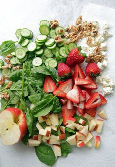 Spinach topped with pieces of apple, strawberry halves, cucumber slices, walnuts, and feta.
