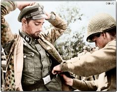 A captured Panzergrenadier of 2nd SS-Panzer-Division Das Reich being searched by a US soldier during the German counter offensive near Mortain (Operation Lüttich), Normandy on August 7-13 1944.
