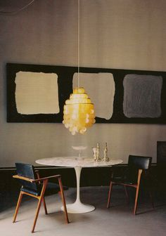 I love the casual and contemporary look of this dining room, with scarcity or mid-century modern furniture and neutral colors. The yellowish ceiling lamp breaks the neutrality and brings interest to the room.