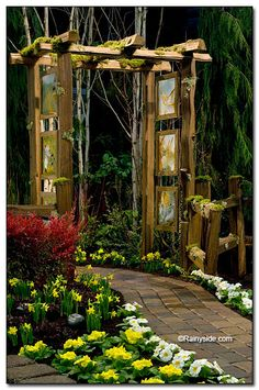 "Beautiful trellis with glass art hanging on sides depicting characters in ""Peter and The Wolf"", by Fancy Plants Gardens."