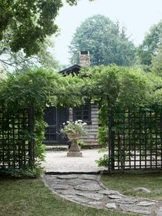 Framed by wisteria, a grecian-style planter holds geraniums and sweet potato vine on this garden patio.