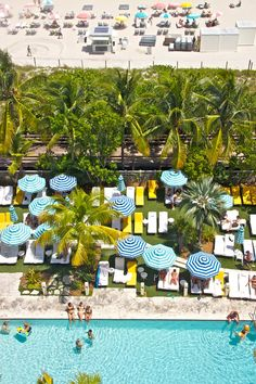 Aerial view of the blue and white striped sun umbrellas and bright yellow sun-loungers by the swimming pool at the Thompson Beach Hotel in Miami. Photo by: Matthew Buck
