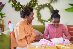 A mother and her daughter sit on a sofa at home in their living room opening a Christmas present Christmas Presents, Flower Girl Dresses, Daughter, Sofa, Living Room, Wedding Dresses, Xmas Gifts, Bride Dresses, Settee