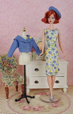 This lovely, fully lined suit features a cropped, double breasted jacket over a classic sheath dress with a coordinating beret.  The scoop neck dress is made from a vintage printed hankie with a floral print in shades of denim blue and yellow. The jacket features a shawl collar, gold buttons over snap closure, and an attached brooch. A classic french beret tops off the look.  This fashion was sewn entirely by hand from a vintage printed hankie, a coordinating blue linen hankie and cotton…