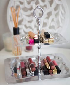 Stack pretty lip glosses and lipsticks on the tiers of a cupcake tray.