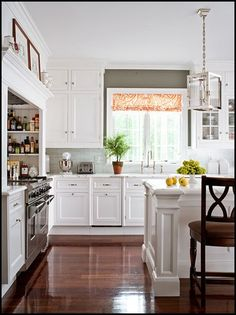 Gray and white kitchen - i love the pop of color in curtains. would die for wood floors in kitchen.