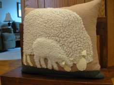 A new pillow that I just finished. It features a mother sheep and her baby grazing in the pasture. Ive used different woolly fabrics for each one.