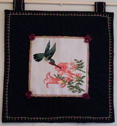 "This beautiful Hummingbird art quilt features a Hummingbird drinking its nectar of life.  The size of the art quilt is 12"" W x 12"" H.  The color"