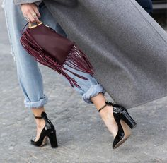 Western reinvented with ripped denim, oxblood fringe clutch and patent black heels