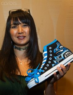 Haida artist and Native American entrepreneur holds up her unique Coast Salish artwork featured on shoes. Marilyn Angel Wynn photography