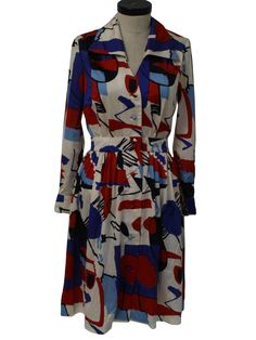 70s -Norman Wiatt Knits- Womens white, red, midnight blue, sky blue and royal blue slinky polyester longsleeve mid length knit dress. A very bold abstract print, with a full skirt, banded and ruched waist, button cuffs, a ruched shoulders, a fold over collar, V-neckline and full length button front. There is a tiny pinhole in the left underarm area, barely visible and a tiny faint rust stain on the back of the collar.