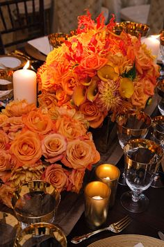 Orange and yellow roses, calla lilies and orange and yellow chrysanthemums look warmer in the glow of tea candles.