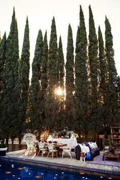 The swimming pool is surrounded by cypress trees.