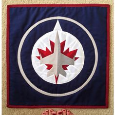 Winnipeg Jets NHL mini quilt that I made for my Dad for Christmas! I drafted a paper piecing pattern for the center portion of the logo myself, and did the larger circles appliqué-style! Paper Piecing Patterns, Quilt Patterns, Miniature Quilts, Mini Quilts, Quilt Making, Jets, Applique, Miniatures, Crafty