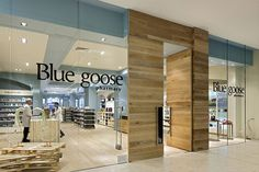 Blue Goose pharmacy Oversized limed timber doors set the scene, that you are entering something different here and balances with the grey blue wall colour referencing the 'plumage morph' of the snow goose when it changes from the 'Blue Goose' to its whiter mature form.