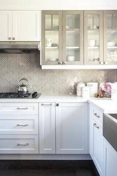 Under white shaker cabinets, a stainless steel vent hood is mounted against Saltillo imports Herringbone Cinder Marble Tiles over an integrated cooktop mounted to white marble countertops above white shaker cabinets adorning polished nickel hardware.