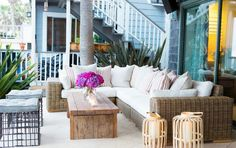 Beachy patio with wicker and wood furniture, lanterns, and metal stools
