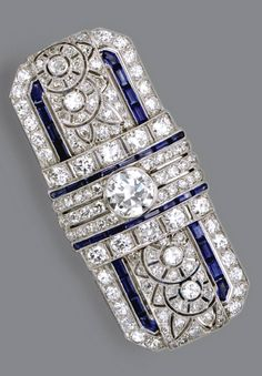 DIAMOND AND SAPPHIRE BROOCH, FRENCH, CIRCA 1930 The openwork rectangular plaque pierced in a floral motif, set in the center with an old European-cut diamond weighing approximately 1.50 carats, completed by numerous old European-cut and single-cut diamonds weighing approximately 4.50 carats, accented further with calibré-cut sapphires, mounted in platinum, French assay marks.