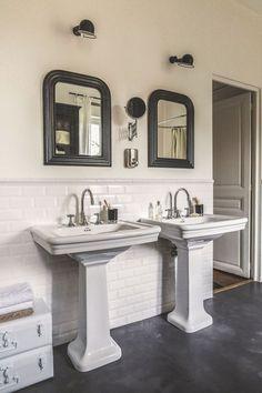 Eléments chinés et d'accessoires contemporains autour de lavabos en porcelaine sur colonne, robinetterie rétro. Carreaux de métro aux murs, sol en béton ciré