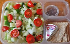 Salad with cucumbers, lettuce, tomato, wasa crackers, laughing cow cheese, balsamic vinaigrette.
