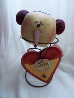 Hes a cutie! A glittered, round snowman head on a rusty bed spring with a glittered heart tag. Perfect size for a cupboard shelf, or even a