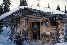 A man wearing a blue flannel shirt and brown pants sits in the open doorway of a log cabin on a winter day.