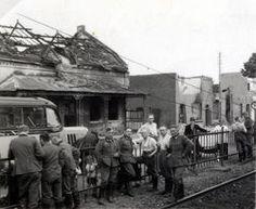 Duitse militairen bij spoorlijn met op achtergrond oorlogsschade, links een...