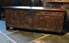 CHESTS / COFFERS - THE TWO PIECE TOP WITH THREE IRON LOOP HINGES ABOVE A MAGNIFICENT CARVED FRONT. THE FRIEZE CARVED WITH BIRDS AND ROSES, ABOVE A SIMULATED FOUR PANELLED FRONT.