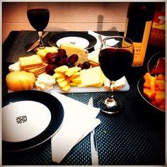 Tábua de queijos e fruta, acompanhada de um vinho tinto alentejano.