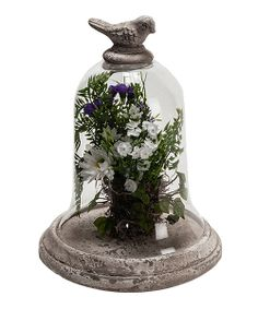 An elegant glass dome looks exceptionally exquisite with special treasures displayed inside. This bird-topped piece offers a protective resting place for a twiggy nest discovery or a vintage figurine.Includes dome and baseFlowers not included11'' H x 8.5'' diameterCeramic / glassImported