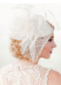 ivory tear shaped hat adorned with large ivory feather peony, feather lily and French dotted veil