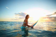 Caucasian girl carrying surfboard in ocean - Caucasian girl carrying surfboard in ocean