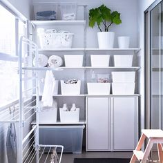 A balcony with white wall shelves, boxes in different sizes, steel cabinets and a drying rack