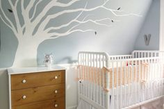 modern white tree mural white and brown cabinet white crib with orange ribbons grey wall with white trim silver owl statue white bed with orange bedsheet
