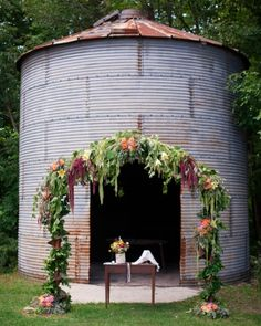 A distressed silo stands behind an arch made of old farm machinery and covered in colorful flowers