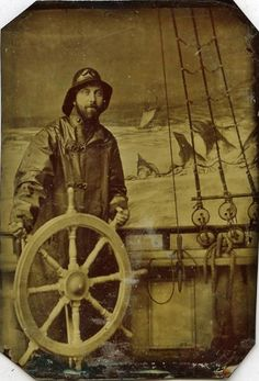 Early novelty photograph - man in oilskins and sou'wester stands at a ship's wheel prop against a painted ocean backdrop