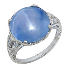 Art Deco Star Sapphire Platinum Ring. Circa 1930s Platinum Diamond and Star Sapphire Ring, 6 Leg Star Sapphire weighing approximately 16 Carats, Violet Blue Hue with noticeable Color Zoning. The ring is further accented with baguette and round Diamonds all set in a pristine exquisite mounting with fine engraving work and a detailed gallery.