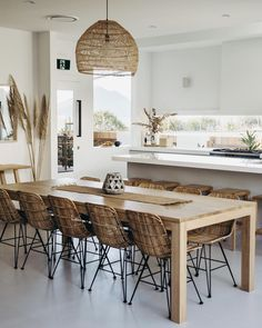 A tropical kitchen with sleek white cabinets, a wicker lampshade, rattan chairs, tropical plants and pampas grass. Dining Room Design, Dining Area, Kitchen Dining, Kitchen Decor, Dining Table, Tropical Kitchen, Rattan Dining Chairs, Furniture Chairs, Kitchen Furniture