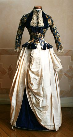 1886 front -  Two-piece dress (bodice and skirt). Sheer silk chine' profiles in the velvet blue. Skirt in ivory silk with inset blue velvet.  ____ Chine' is a tissue in which the warp yarns are printed motif, often floral, before being woven. This gives the drawings on the fabric a fuzzy appearance after weaving. ____ (translated from Italian by Google)