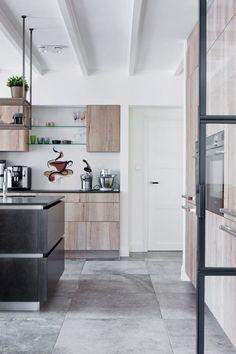 Deze industriële keuken is voorzien van een donker kookeiland, grote grijze tegels, keukenfronten met houtfinish en andere Loft-details in industrie-stijl.   #keuken #keukens #loft #snaidero #snaiderocucine #kookeiland #keukenblok #keukeneiland #koken #interieur #wonen #kitchen #kitchendesign #inrichting #modernwonen #industrieelwonen Kitchen On A Budget, Kitchen Remodel, Kitchen Decor, Divider, Table, Room, Inspiration, Furniture, Design