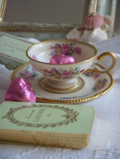 gold leafed tea cup with chocolates and a vintage book limoges and LaDuree
