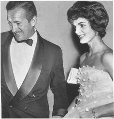 "Actor David Niven recalls dancing with Jackie at New York's El Morocco in 1958: ""JFK sat in the back room and when I asked Jackie why he wouldn't join us, she laughed and said, 'He doesn't want to be photographed doing something so frivolous… He wants to be President.'"" Her silk tulle gown is adorned with tiny silk flowers, and on her wrist is the diamond bracelet that was a wedding gift from her husband."