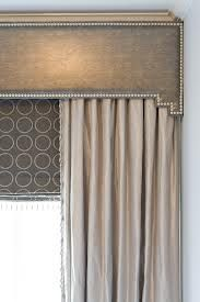 cornice box valance in cream fabric w/ nailhead trim to match bed frame; grey solar touch-draw blinds in back, covered by semi-sheer soft white  curtains in front