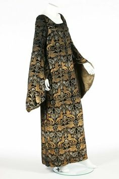 * Maria Gallenga stencilled velvet medieval style dress, circa 1925, the black silk velvet printed overall in gold and silver with birds and lions, with gold lamé lined hanging sleeves