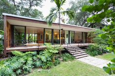 The covered front porch of this husband and wife designed Miami home is protected by hinged slats of western red cedar that run all along the street-facing side of the house.  The conditioned space = 1500 ft.² while the covered decks = another 800 ft.² of indoor/outdoor living space; for a grand total of 2300 ft.²  04/17