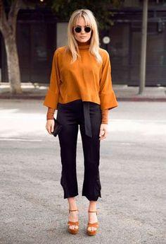 Street style look com camel turtleneck, calça preta e sandália marrom.