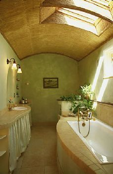 cob house bathroom - I like how relaxing this looks. But I would just organize under sicks in wicker baskets without the curtain.