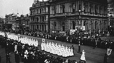 Contingent of (Voluntary Aid Detachment) VAD nurses marching along King William Street, Adelaide, South Australia with Effie Green leading them; the procession was in aid of a Red Cross fundraising drive, WWI ~
