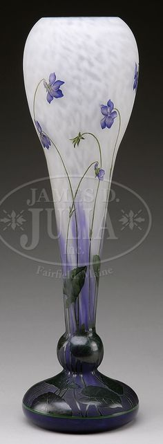 """DAUM NANCY CAMEO & ENAMELED VASE. Large Daum vase has purple bulbous foot with enameled green cameo leaves giving way to slender green enameled cameo stems and leaves leading to cameo violets with shaded purple enamel all against a mottled purple shading to white background. Signed on the side in cameo """"Daum Nancy"""" with cross of Lorraine. Vase also has remnants of original retailer's paper label """"Coin de Westende"""". Vase retains Sotheby's string tag."""