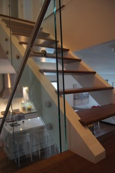 This floating staircase with open treads and glass railings is a focal highlight in this custom designed home.